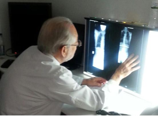 Dr. Candelario flores observando una radiografía